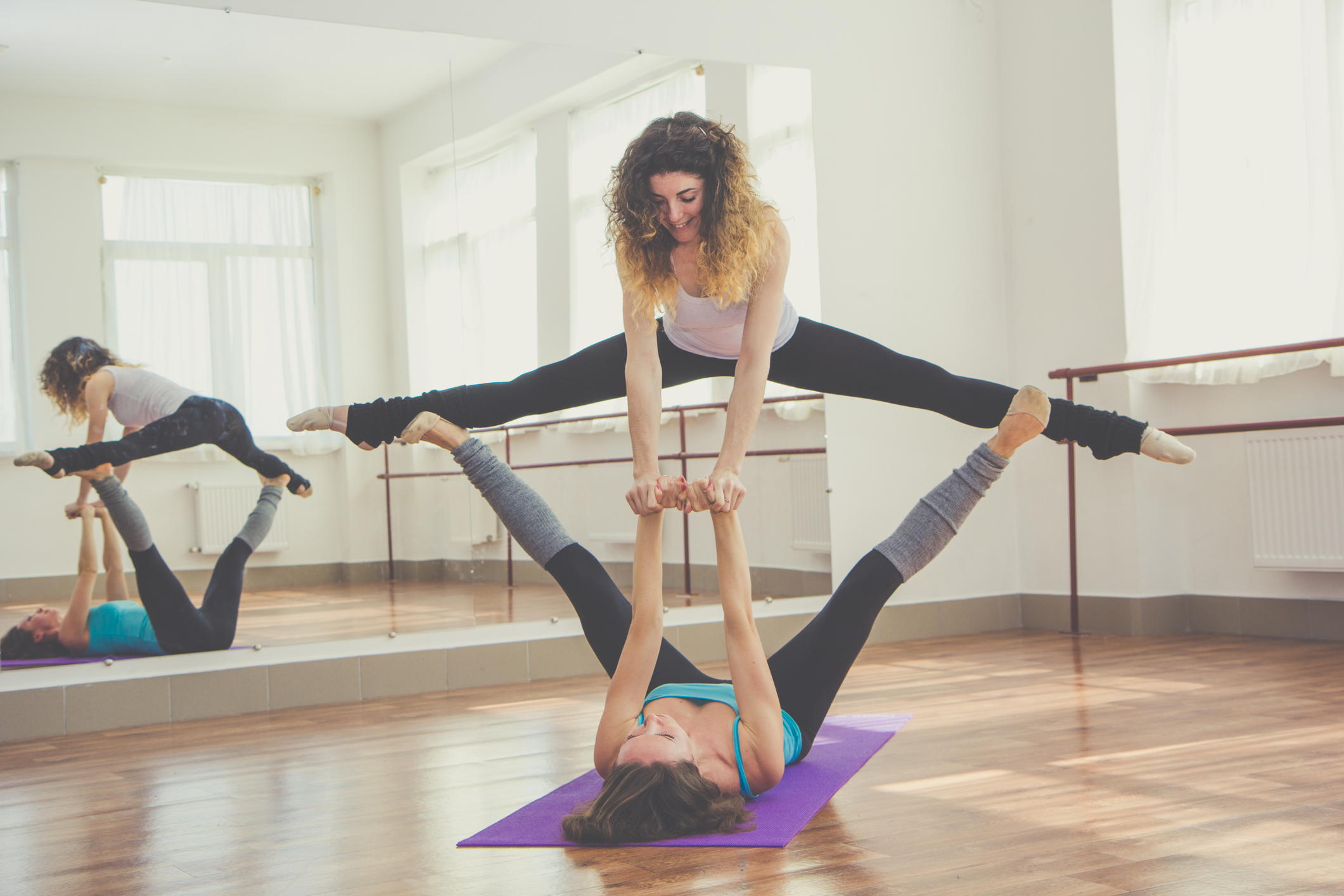 Two fit women are doing balance exercise